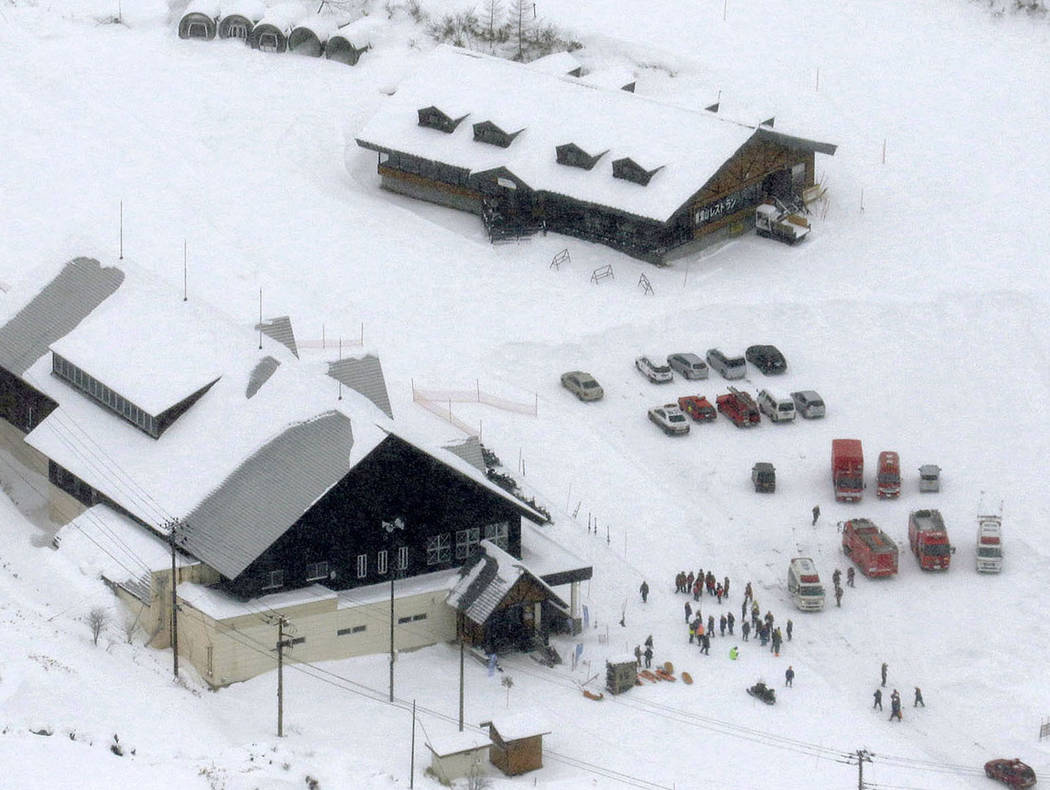 Fire trucks and ambulances are parked at a ski resort in Kusatsu, central Japan, after Mount Kusatsu-Shirane erupted Tuesday, Jan. 23, 2018. A disaster official said the volcano erupted and caused ...