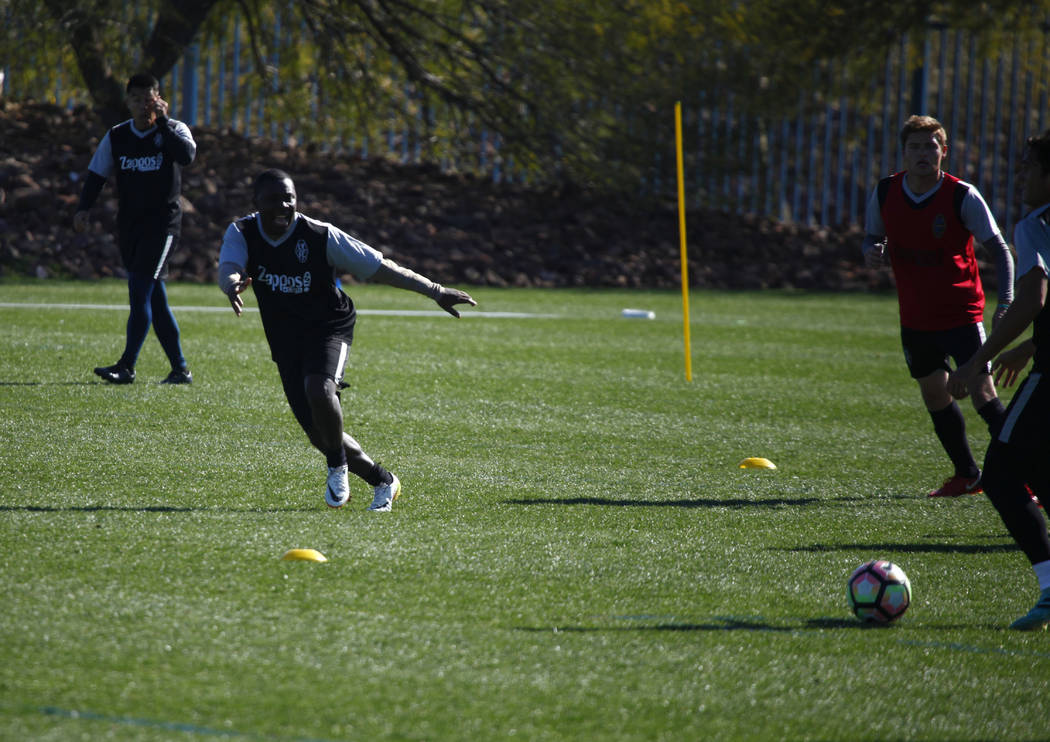 Former American soccer prodigy and U.S. national team member Freddy Adu, white shoes, runs toward the soccer ball as he tries out for the Las Vegas Lights FC at the team's practice field in Las Ve ...