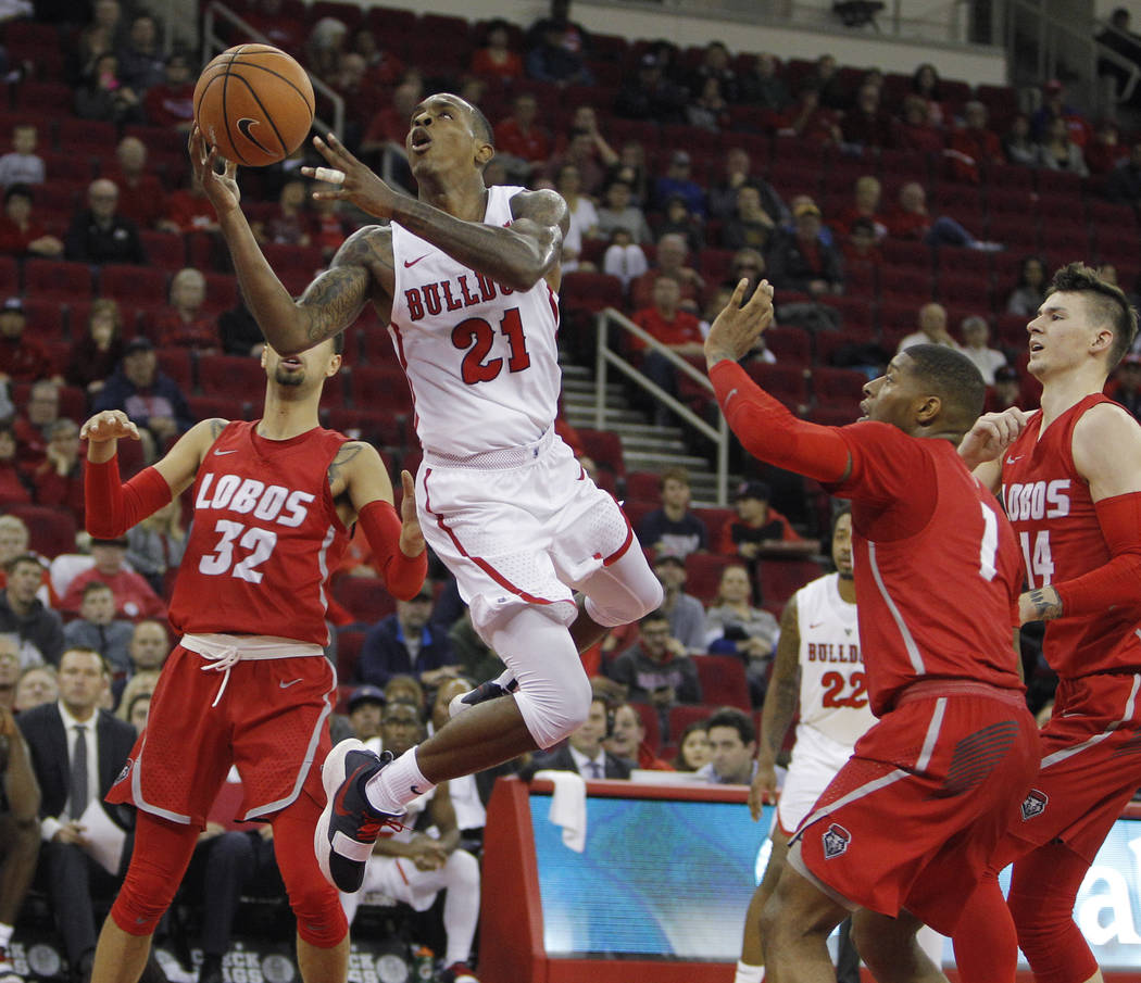 Fresno State's Deshon Taylor soars in for a layup against New Mexico's Anthony Mathis, left and Chris McNeal, center, during the second half of an NCAA college basketball game in Fresno, Calif., S ...