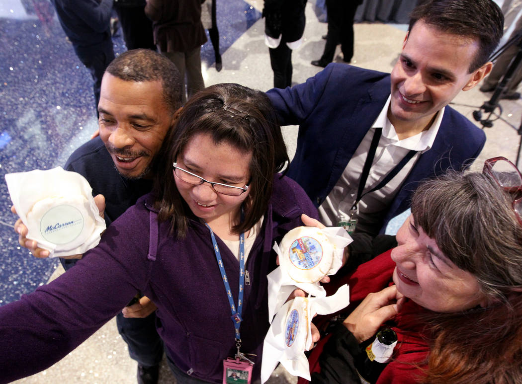 Employees, from left, Alonzo Ledford, Lorraine Kae Cruz, Jay Alvarez and Caryn Hatalla pose for a selfie with decorative cookies at McCarran International Airport during a celebration Wednesday, J ...