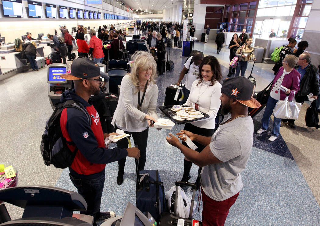 Linda Healey, second from left, and Melissa Nunnery DeFrank hand out cookies to Larry Dues, left, and his brother Darren Dues, both of Houston, at McCarran International Airport during a celebrati ...