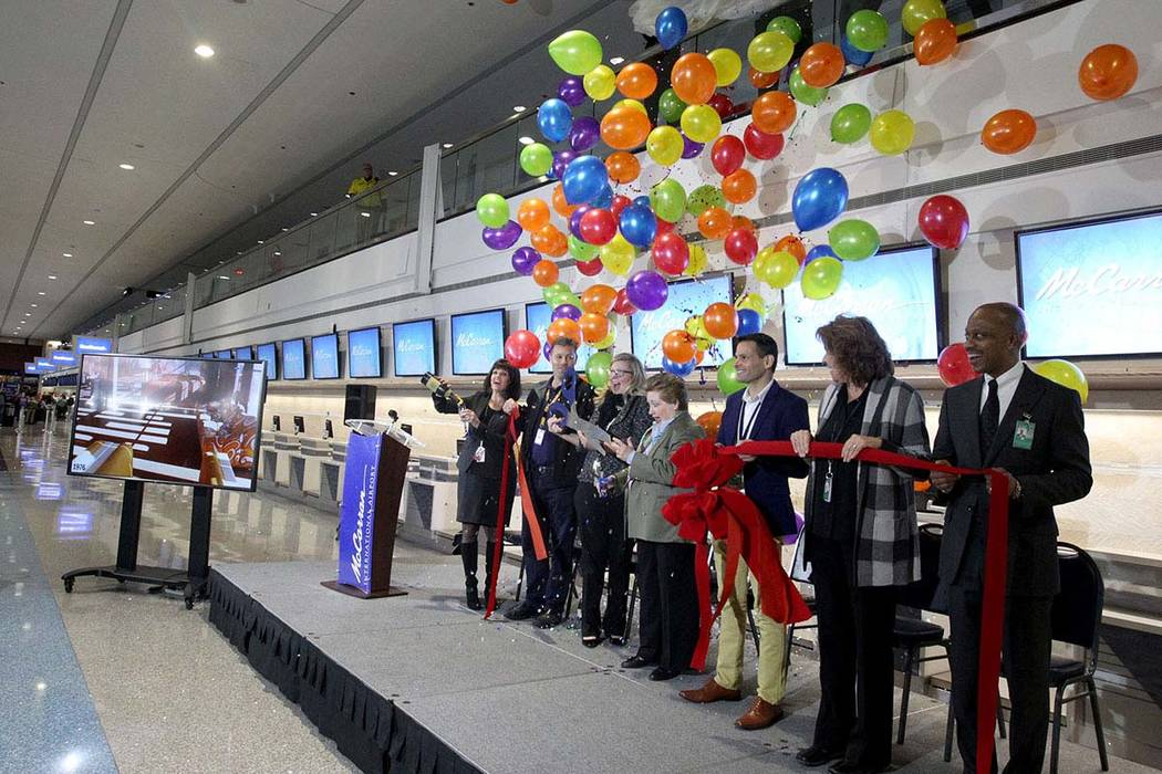 Balloons and confetti drop at McCarran International Airport during a celebration Wednesday, Jan. 24, 2018, marking the completion of a $30 million Terminal 1 renovation project. Officials, from l ...