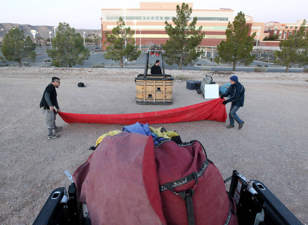 Daniel Liberti, rear, a hot air balloon pilot with Rainbow Ryders, prepares for an early morning flight with field operations manager Danny Breeden, left, and Andrew Pieper at an empty southwest L ...