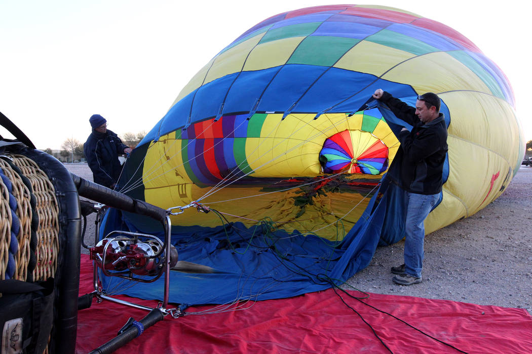 Daniel Liberti, right, a hot air balloon pilot with Rainbow Ryders, prepares for an early morning flight with Andrew Pieper at an empty southwest Las Vegas lot Wednesday, Jan. 24, 2018. K.M. Canno ...