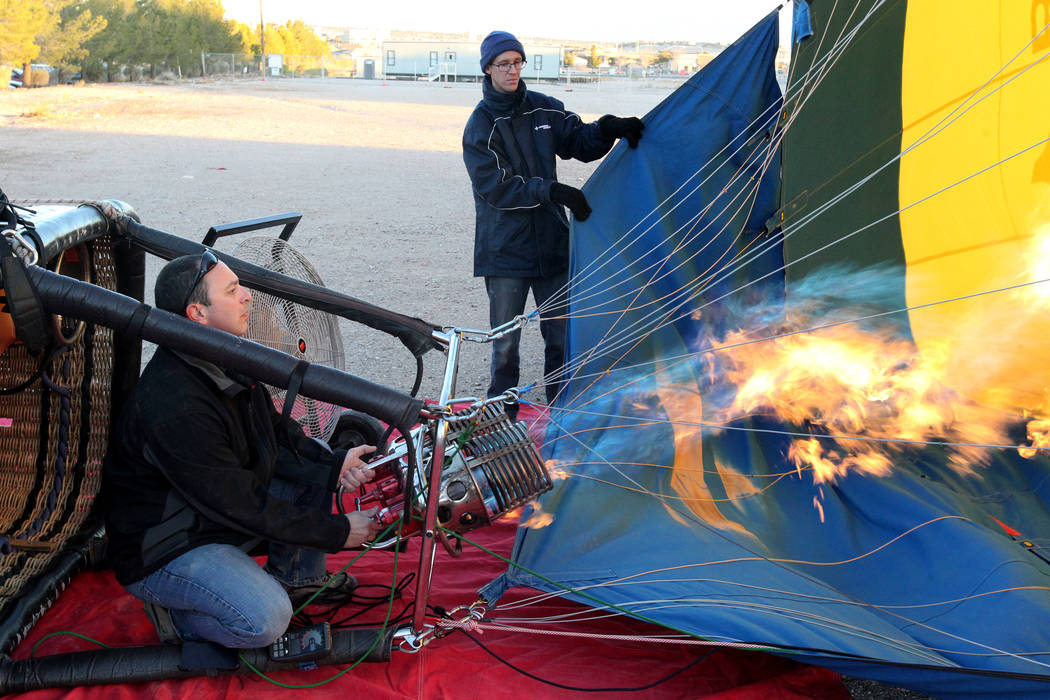 Daniel Liberti, left, a hot air balloon pilot with Rainbow Ryders, prepares for an early morning flight with Andrew Pieper at an empty southwest Las Vegas lot Wednesday, Jan. 24, 2018. K.M. Cannon ...