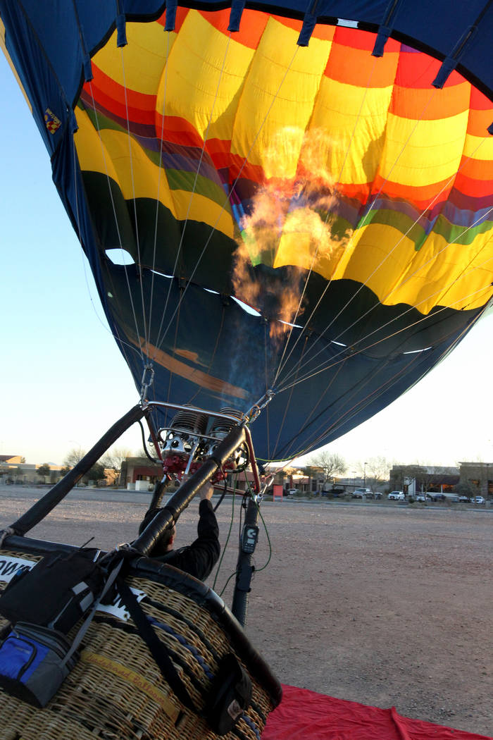 Daniel Liberti, a hot air balloon pilot with Rainbow Ryders, fires up his balloon as it tilts upright for an early morning flight at an empty southwest Las Vegas lot Wednesday, Jan. 24, 2018. K.M. ...