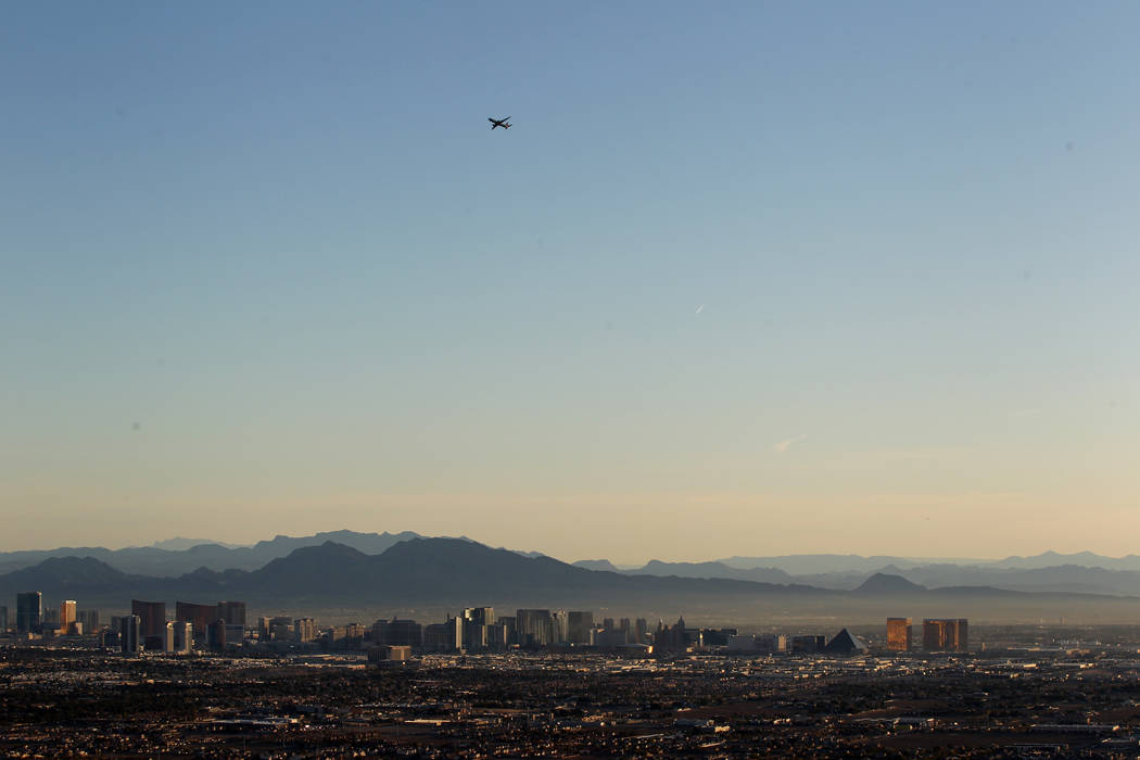 A plane takes off over the Strip as seen from a hot air balloon piloted by Daniel Liberti of Rainbow Ryders during an early morning flight in southwest Las Vegas Wednesday, Jan. 24, 2018. K.M. Can ...