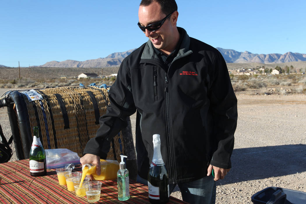 Daniel Liberti, a hot air balloon pilot with Rainbow Ryders, prepares Champagne and orange juice after landing near Blue Diamond and Fort Apache roads in Las Vegas Wednesday, Jan. 24, 2018. K.M. C ...