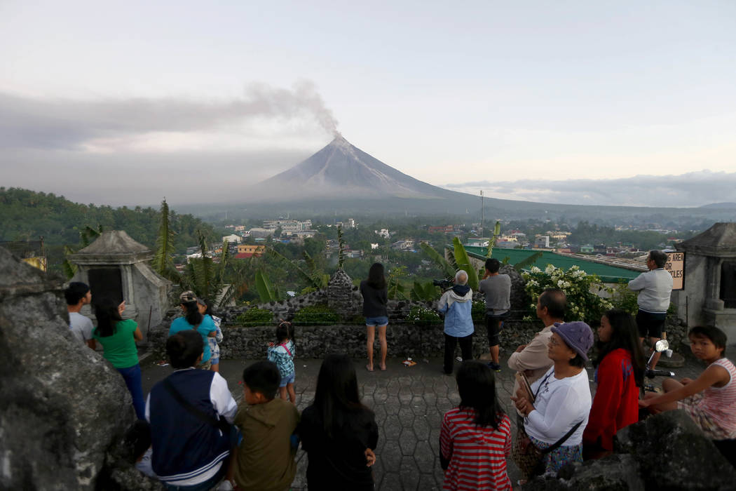 Residents watch as Mayon volcano spews ash anew during its eruption for the second straight day Tuesday, Jan. 23, 2018 as seen from Legazpi city, Albay province, around 340 kilometers (200 miles)  ...