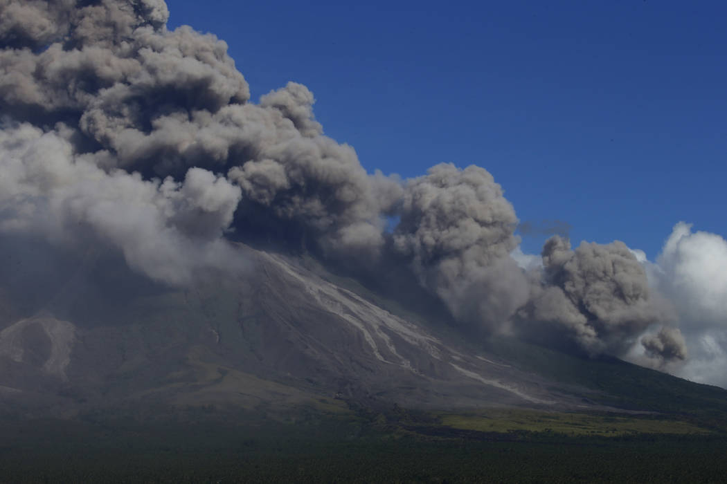 Pyroclastic materials cascade down the slopes of Mayon volcano as it erupts anew Tuesday, Jan. 23, 2018 as seen from Legazpi city, Albay province, around 340 kilometers (200 miles) southeast of Ma ...