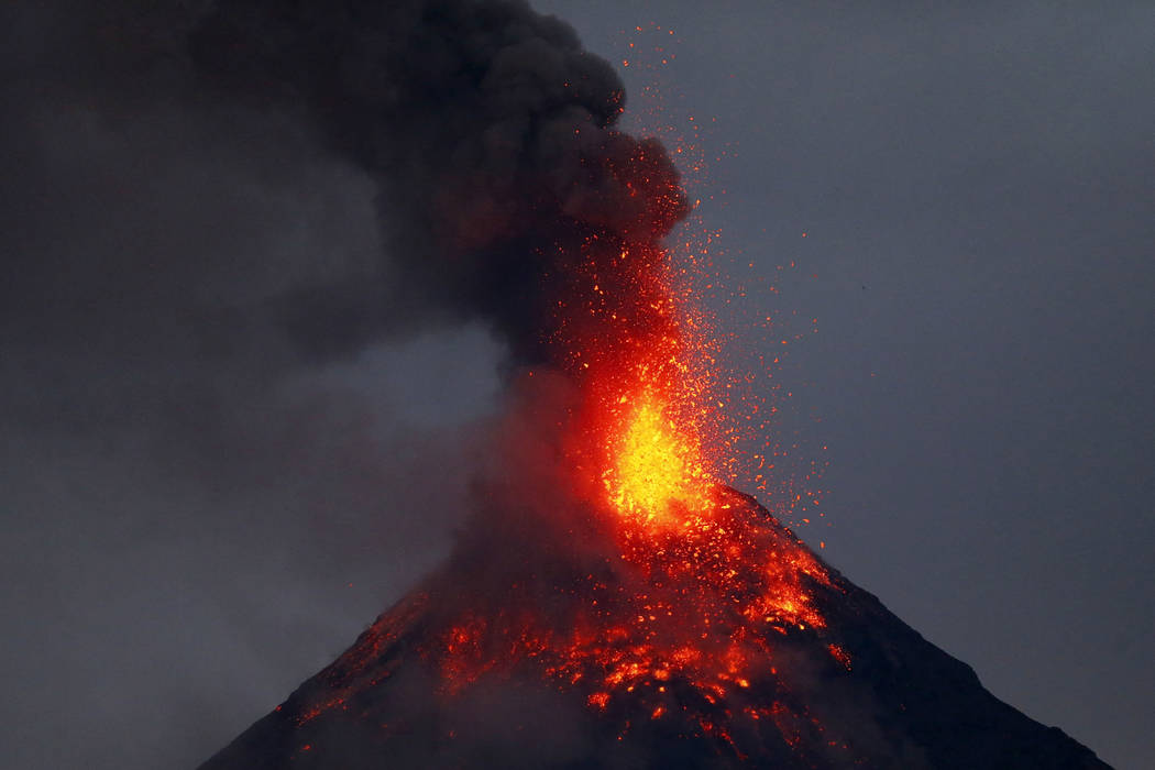 Mayon volcano spews red-hot lava in another eruption as seen from Legazpi city, Albay province, roughly 200 miles (340 kilometers) southeast of Manila, Philippines, Tuesday, Jan. 23, 2018. (AP Pho ...