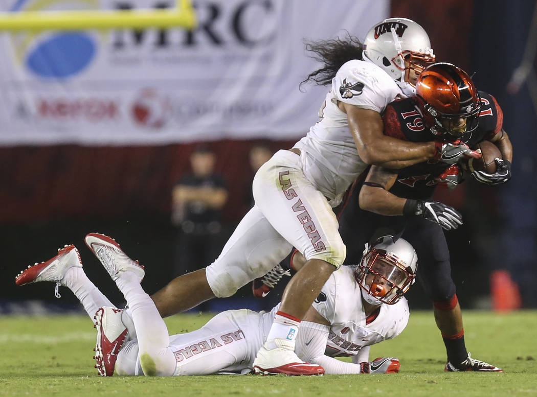 San Diego State running back Donnel Pumphrey (19) is tackled by UNLV linebacker Tau Lotulelei (55) and UNLV defensive lineman Tui Maloata (91) during a football game at Qualcomm Stadium in San Die ...