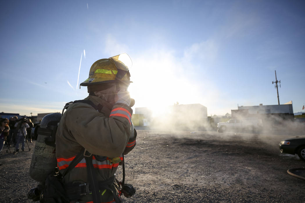 A firefighter puts on his mask before extinguishing a car fire during a car arson demonstration and training seminar at the Clark County Fire Academy in Las Vegas, Friday, January 26, 2018. Richar ...