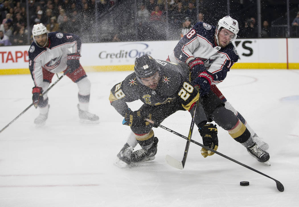 Vegas Golden Knights left wing William Carrier (28) and Columbus Blue Jackets center Pierre-Luc Dubois (18) fight for possesion in the NHL game at T-Mobile Arena Las Vegas, Tuesday, Jan. 23, 2018. ...