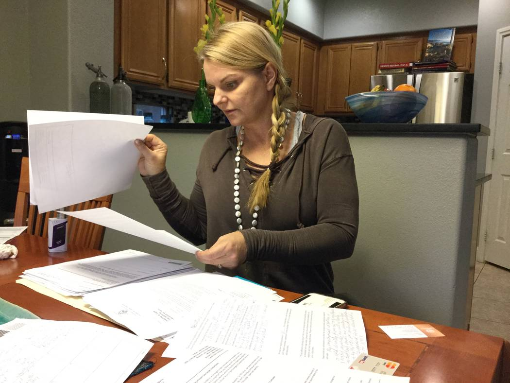 Christine Caria, at her Las Vegas home on Tuesday, Jan. 9, 2018, reviews the paperwork she needed in order to apply for financial assistance after surviving and sustaining injuries related to the  ...