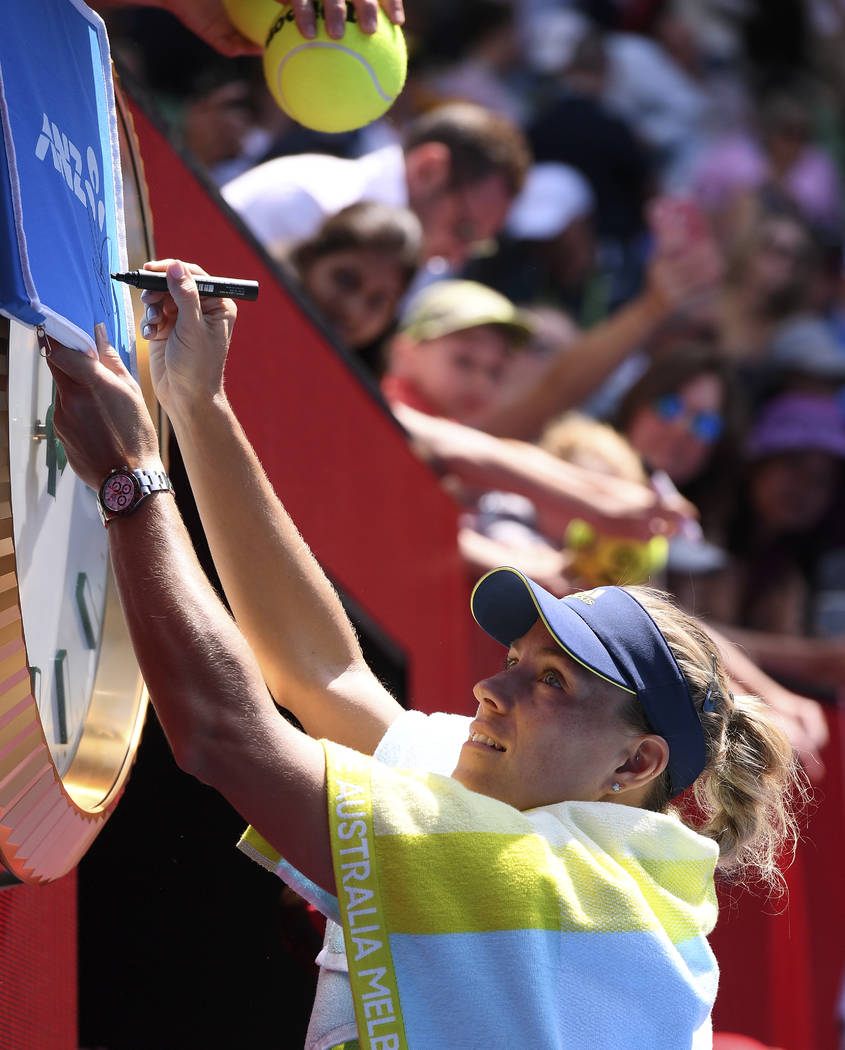 Germany's Angelique Kerber signs autographs after defeating United States' Madison Keys in their quarterfinal at the Australian Open tennis championships in Melbourne, Australia, Wednesday, Jan. 2 ...