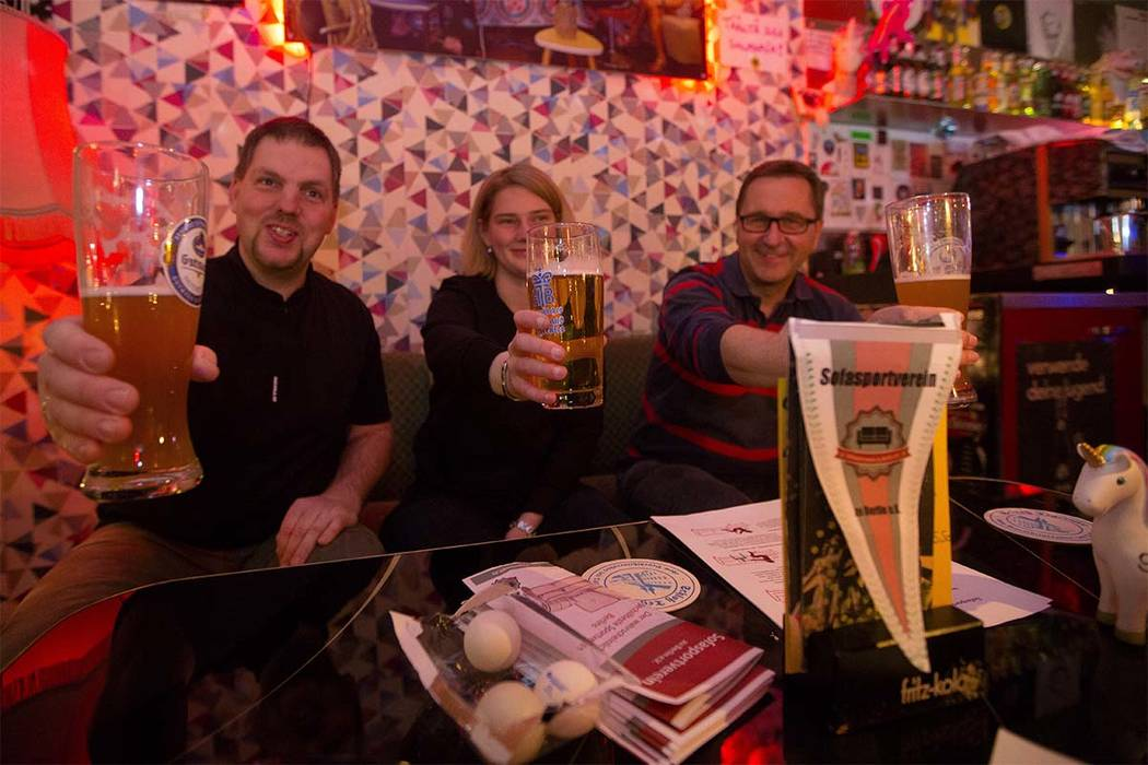 In this Jan. 11, 2018 photo, Torben Bertram, (from left), Patricia Bernreuther and Norbert Buddendick hold a glasa of beer during a training session of Germany's first sofa sports association at t ...