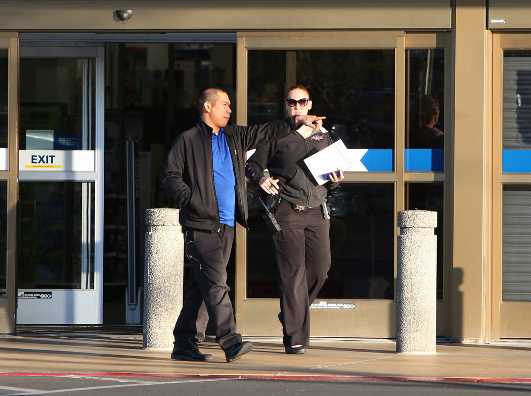 A Best Buy employee and a Las Vegas police detective exit the store Tuesday, Jan. 23, 2018, in Las Vegas. A man was kidnapped and carjacked in front of the Best Buy at 6950 Arroyo Crossing, near t ...