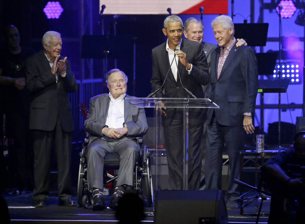 Former President Barack Obama, speaks as fellow former Presidents, from left, Jimmy Carter, George H.W. Bush, George W. Bush, and Bill Clinton look on during a hurricanes relief concert in College ...