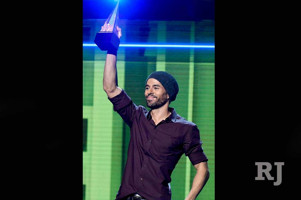 Enrique Iglesias accepts the artist of the year award at the Latin American Music Awards in Los Angeles, Oct. 26, 2017. Iglesias is suing Universal Music Group in a dispute over how much he is pai ...