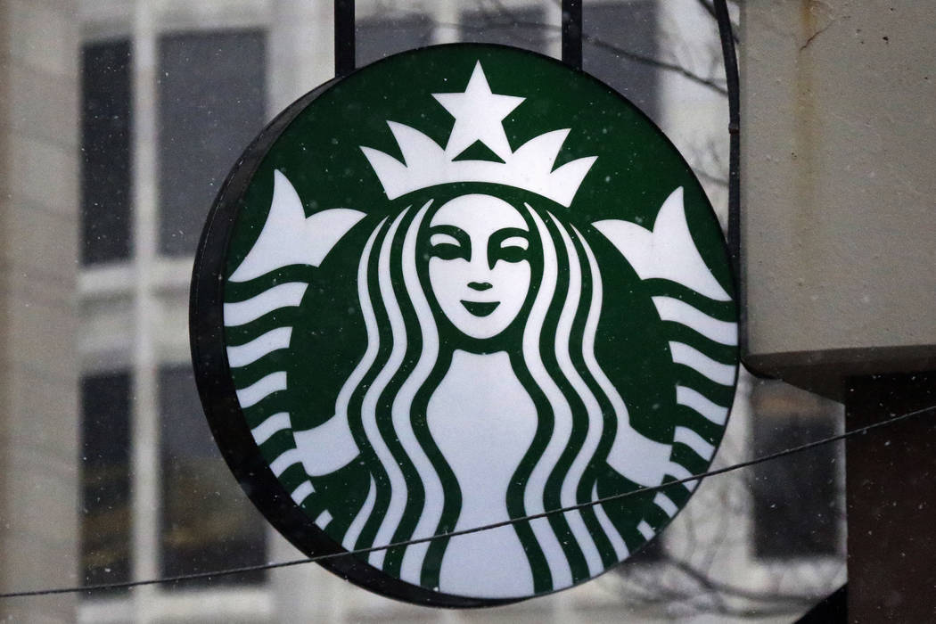 FILE - This Tuesday, March 14, 2017, file photo shows the Starbucks logo on a shop in downtown Pittsburgh. Starbucks is giving its U.S. workers pay raises and stock bonuses in 2018, citing recent  ...