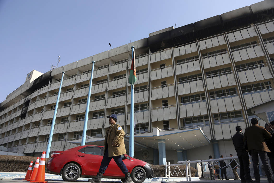 An Afghan security stand guard walks in front of the Intercontinental Hotel in Kabul, Afghanistan, Tuesday, Jan. 23, 2018. Survivors of the Taliban attack on Kabul's Intercontinental Hotel gave ha ...