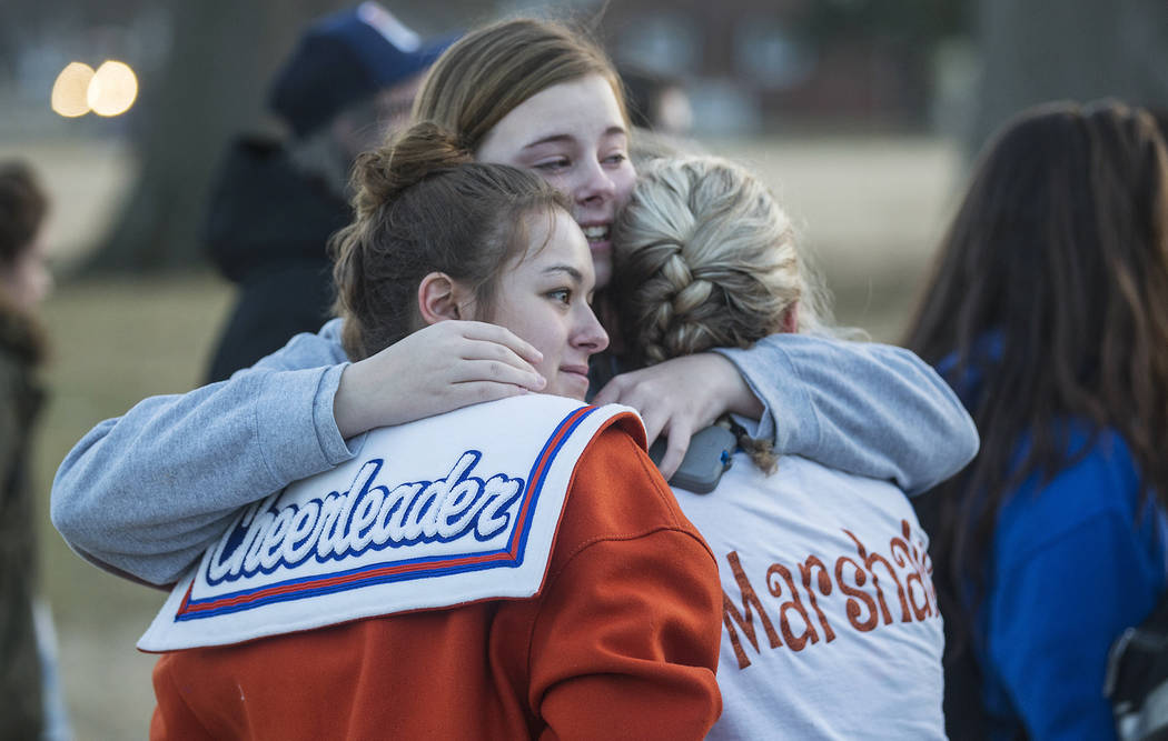 Alyssa Edging, center, a student at McCracken County High School, embraces Erica Johnson, left, and Abigail Hicks, both juniors at Marshall County High School in Benton, Ky., following a prayer vi ...