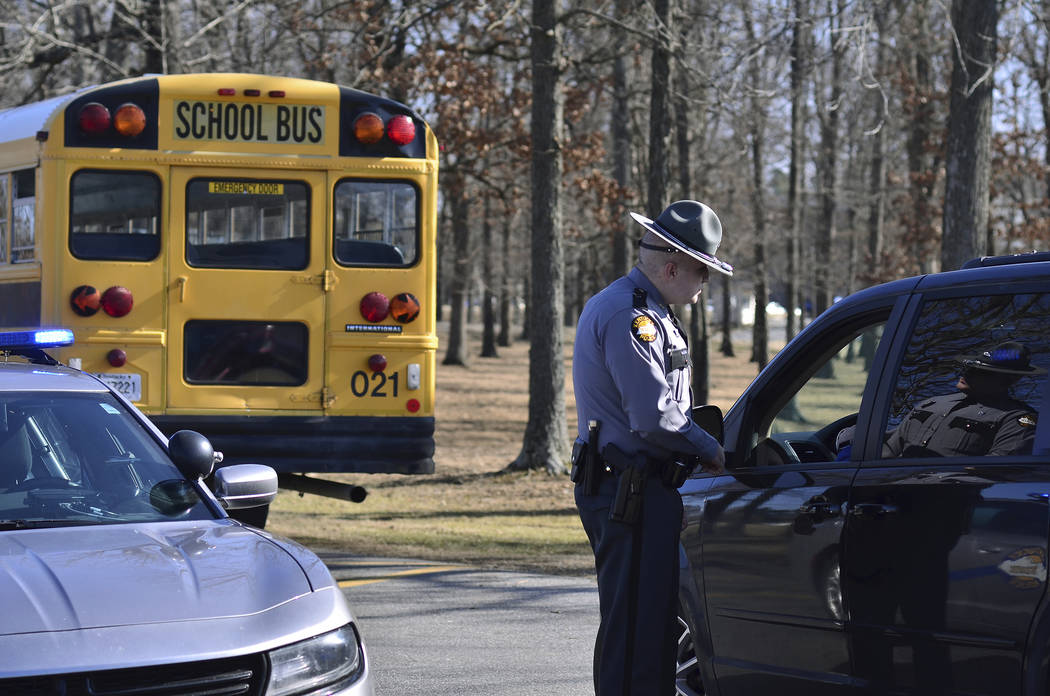 A Kentucky State Police trooper checks with a motorist entering Marshall County High School Wednesday, Jan. 24, 2018, near Benton, Ky. Two students died and another 18 people were injured in a sho ...