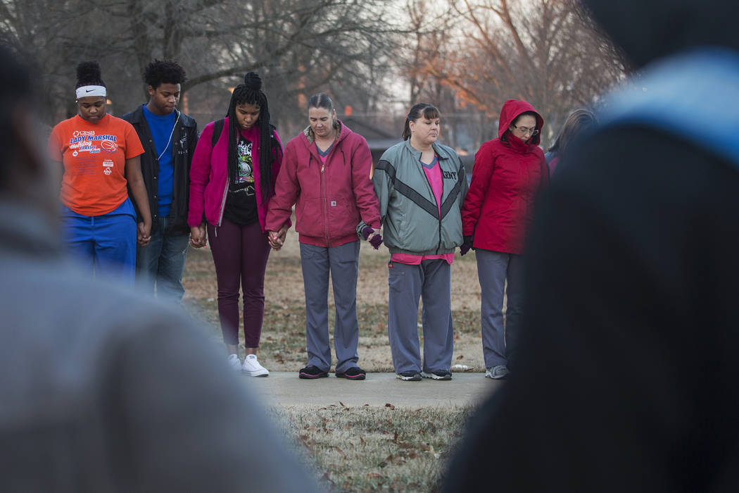 Students and community members hold hands in prayer before classes at Paducah Tilghman High School in Paducah, Ky., Wednesday, Jan. 24, 2018. The gathering was held for the victims of the Marshall ...