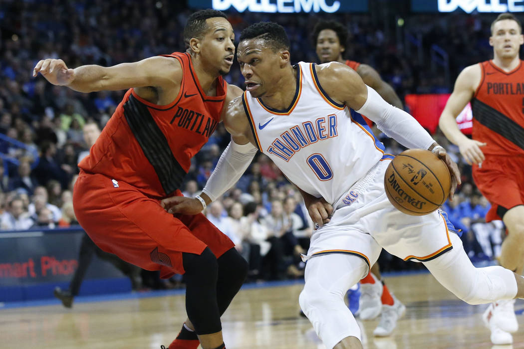 Oklahoma City Thunder guard Russell Westbrook (0) drives around Portland Trail Blazers guard C.J. McCollum during the first quarter of an NBA basketball game in Oklahoma City, Tuesday, Jan. 9, 201 ...