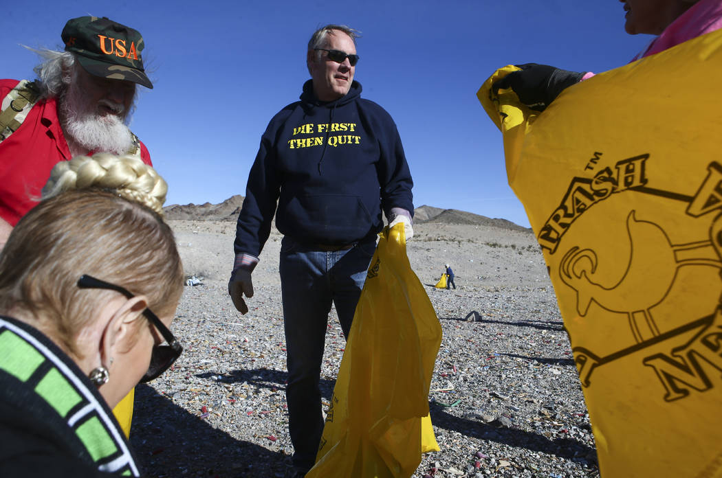 Interior Secretary Ryan Zinke, center, talks with Cheryl Prater, right, while joining volunteers in cleaning up a shooting range area on public land along Las Vegas Boulevard just south of Sloan o ...