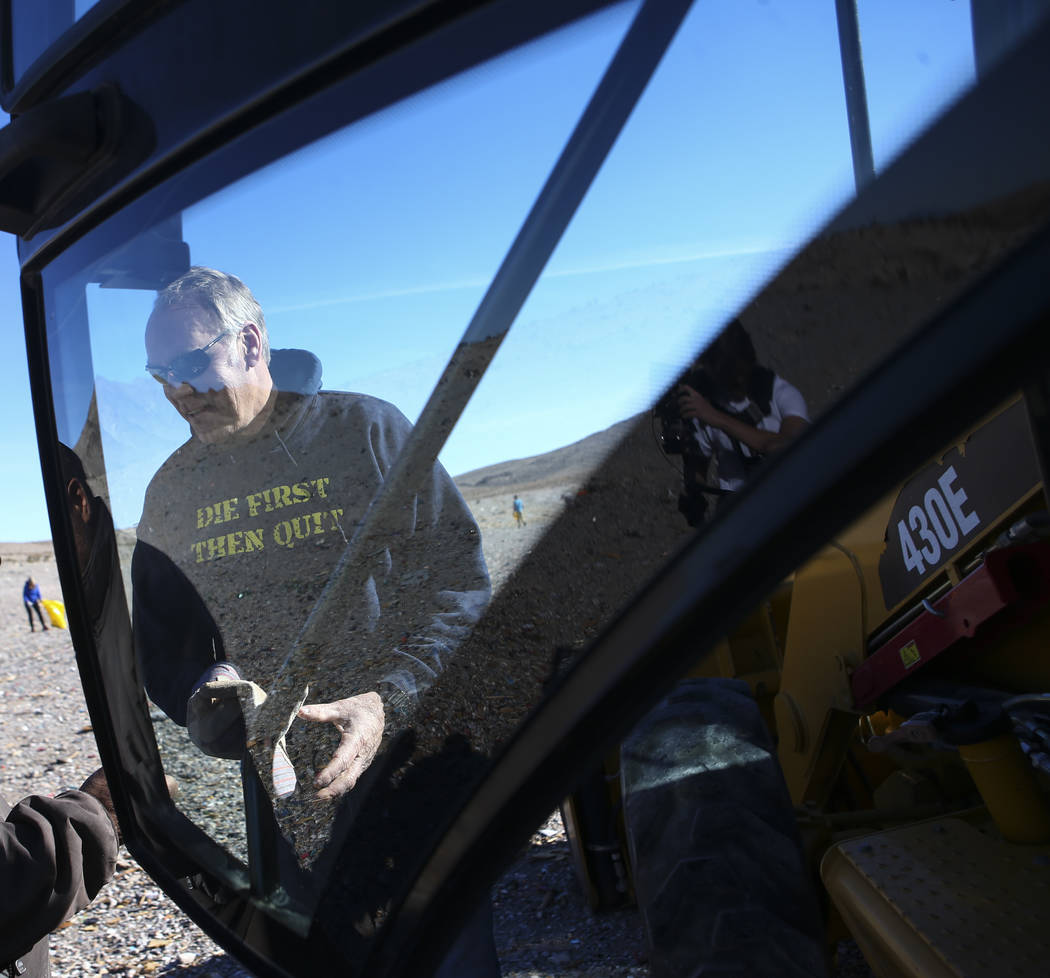 Interior Secretary Ryan Zinke gets ready to jump into a backhoe loader while joining volunteers and Bureau of Land Management employees in cleaning up a shooting range area on public land along La ...
