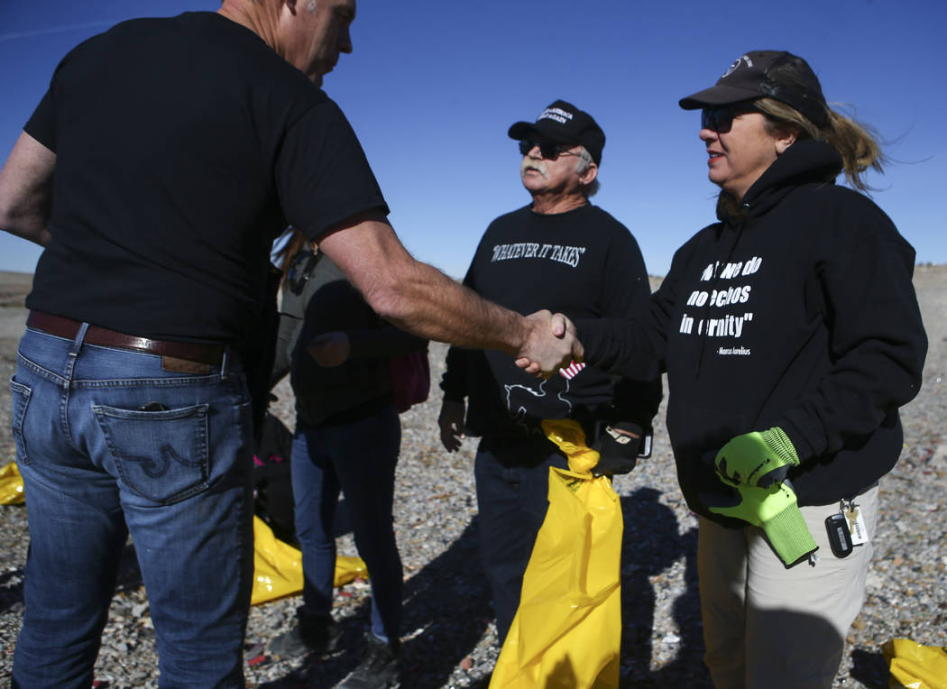 """Interior Secretary Ryan Zinke, left, greets Cliven Bundy supporters Robert """"Lil' Dog"""" Crooks, center, and Diana McNamara while joining volunteers in cleaning up a shooting range  ..."""