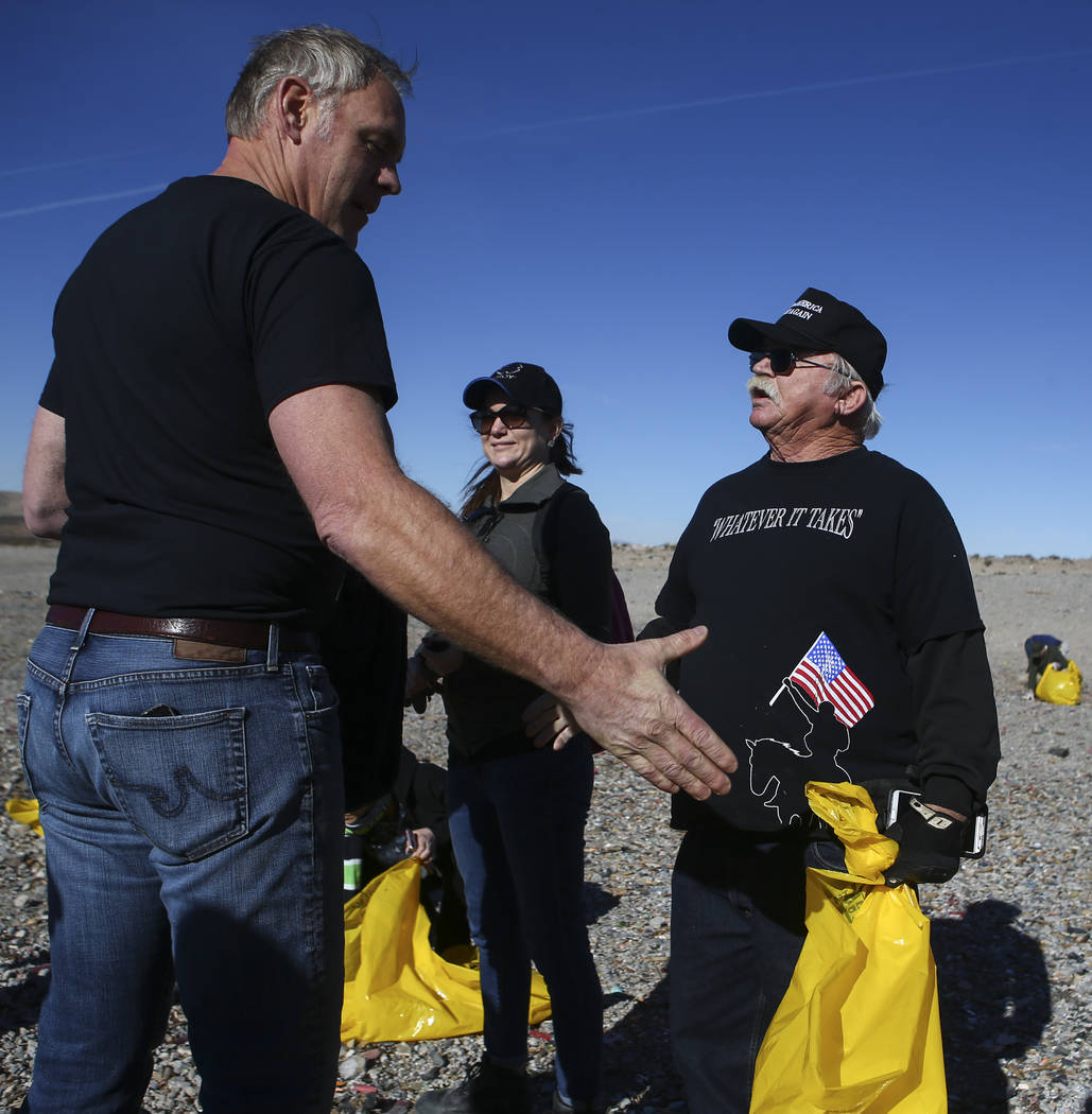 """Interior Secretary Ryan Zinke, left, talks with Robert """"Lil' Dog"""" Crooks, right,  a supporter of Cilven Bundy who camped out in Bunkerville, while joining volunteers in cleaning  ..."""