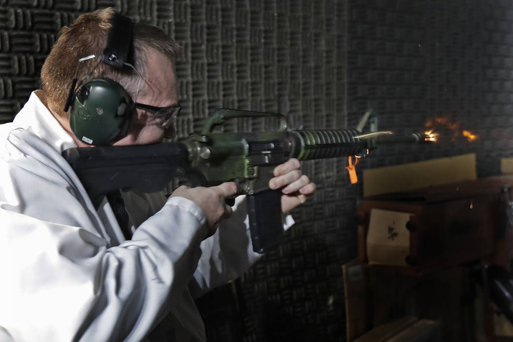 Washington Rick Wyant, supervisor of the forensic firearms unit at the Washington State Patrol crime laboratory in Seattle, test fires a semi-automatic rifle that has been fitted with a so-called  ...