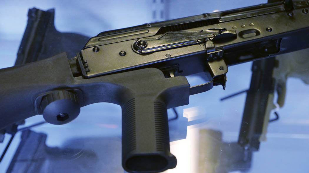 "A device called a ""bump stock"" is attached to a semi-automatic rifle at the Gun Vault store and shooting range in South Jordan, Utah on Oct. 4, 2017. (AP Photo/Rick Bowmer, File)"
