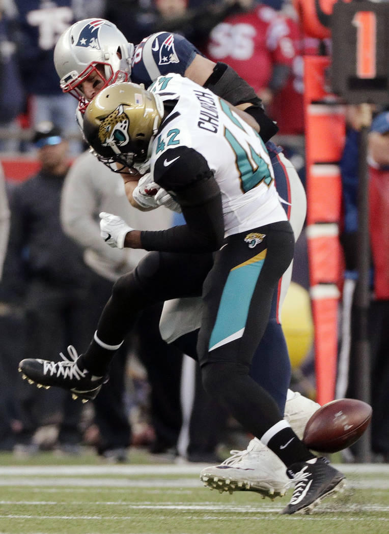 New England Patriots tight end Rob Gronkowski, rear, is hit by Jacksonville Jaguars safety Barry Church as he breaks up a pass during the first half of the AFC championship NFL football game, Sund ...