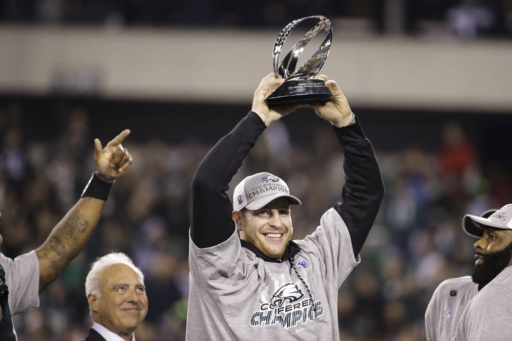 Philadelphia Eagles' Carson Wentz holds the George Halas Trophy after the NFL football NFC championship game against the Minnesota Vikings Sunday, Jan. 21, 2018, in Philadelphia. (AP Photo/Matt Ro ...