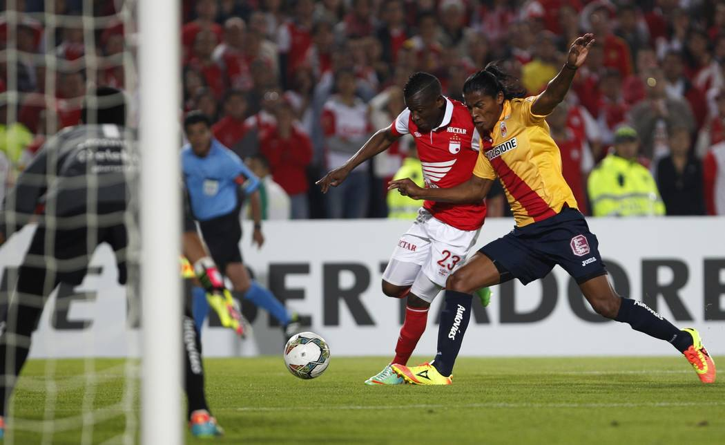 Joel Huiqui of Mexico's Monarcas, right, fights for the ball with Jefferson Cuero of Colombia's Independiente Santa Fe, second right, during a Copa Libertadores soccer match in Bogota, Colombia, T ...