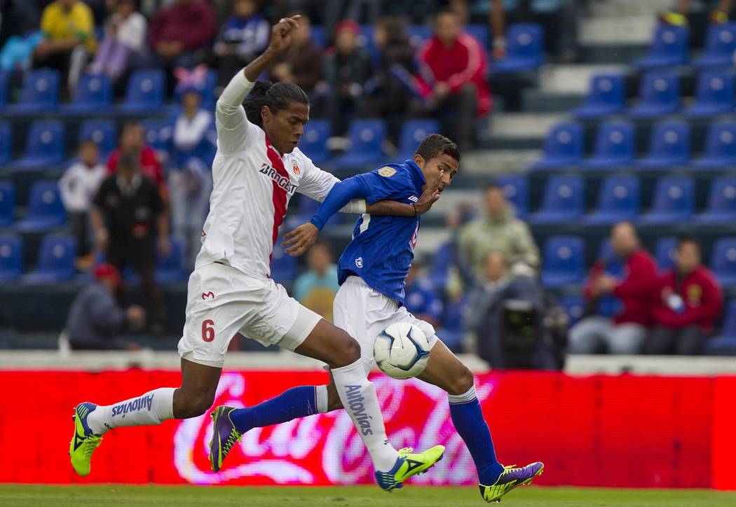 Cruz Azul's Joao Rojas, right, fights for the ball with Morelia's Joel Huiqui during a Mexican soccer league match in Mexico City, Saturday, Nov. 2, 2013. (AP Photo/Christian Palma)