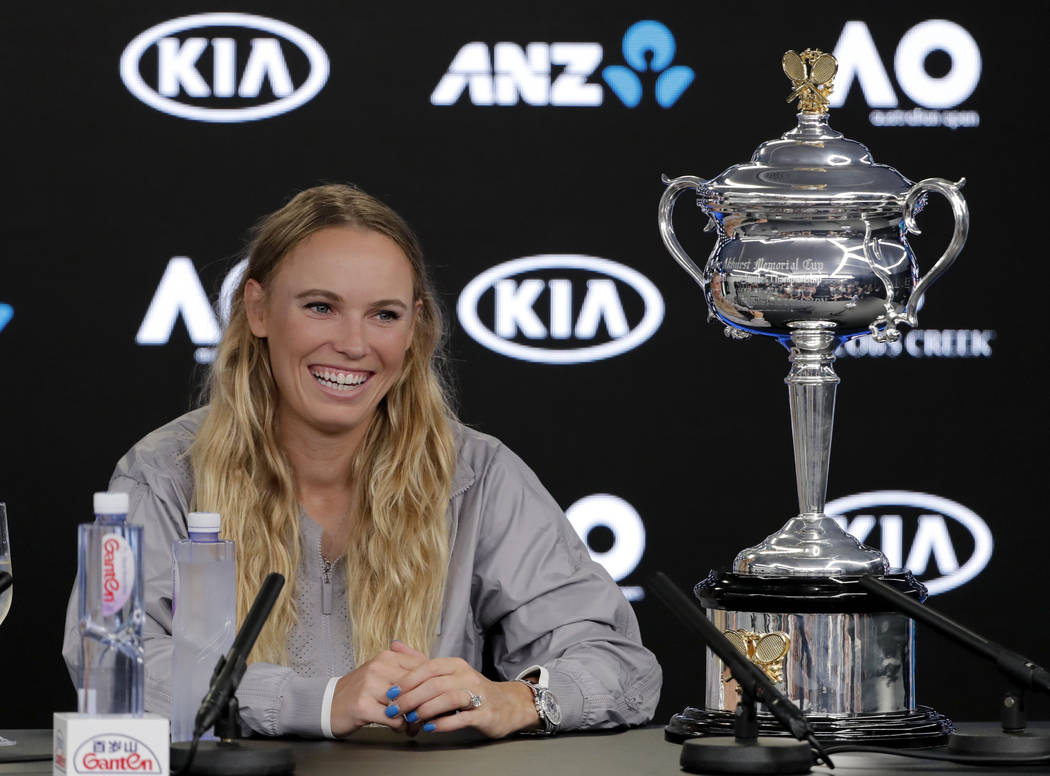 Denmark's Caroline Wozniacki smiles at a press conference with her trophy after defeating Romania's Simona Halep in the women's singles final at the Australian Open tennis championships in Melbour
