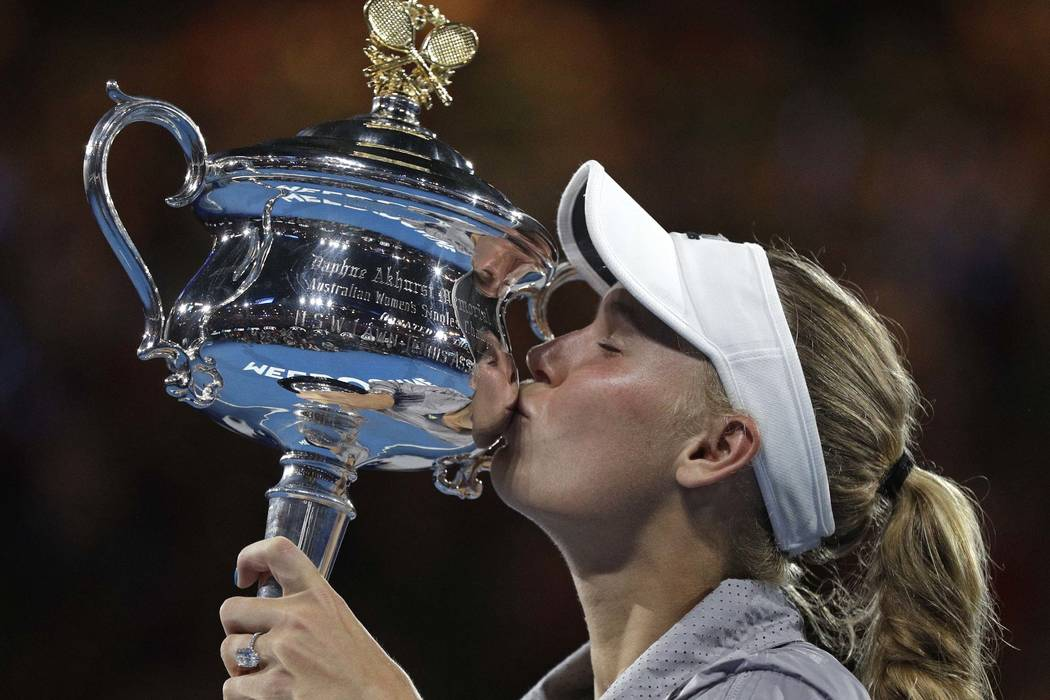 Denmark's Caroline Wozniacki kisses her trophy after defeating Romania's Simona Halep during the women's singles final at the Australian Open tennis championships in Melbourne Australia Saturday