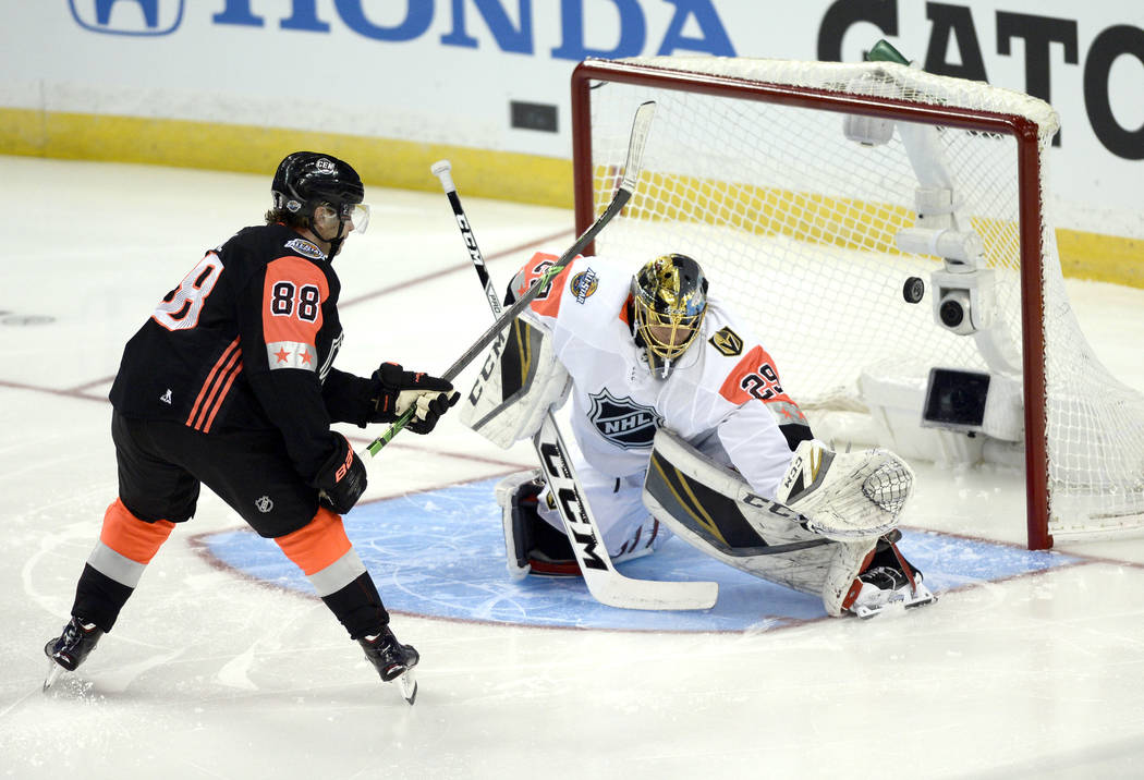 Central Division's Patrick Kane, left, of the Chicago Blackhawks, shoots wide of Pacific Division goalie Marc-Andre Fleury, of the Vegas Golden Knights, during the NHL hockey All-Star game Sunday, ...