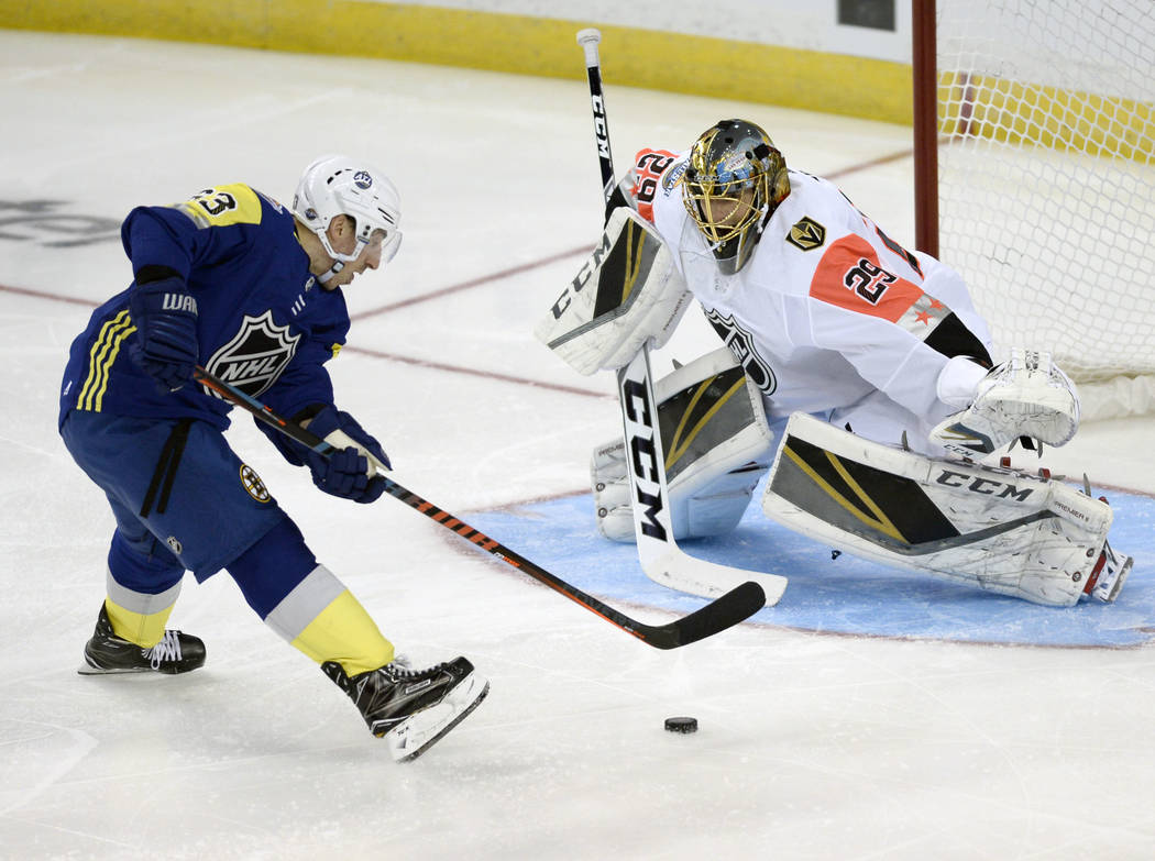 Atlantic Division's Brad Marchand, left, of the Boston Bruins, advances against Pacific Division goalie Marc-Andre Fleury, of the Vegas Golden Knights, during the NHL hockey All-Star game Sunday,  ...