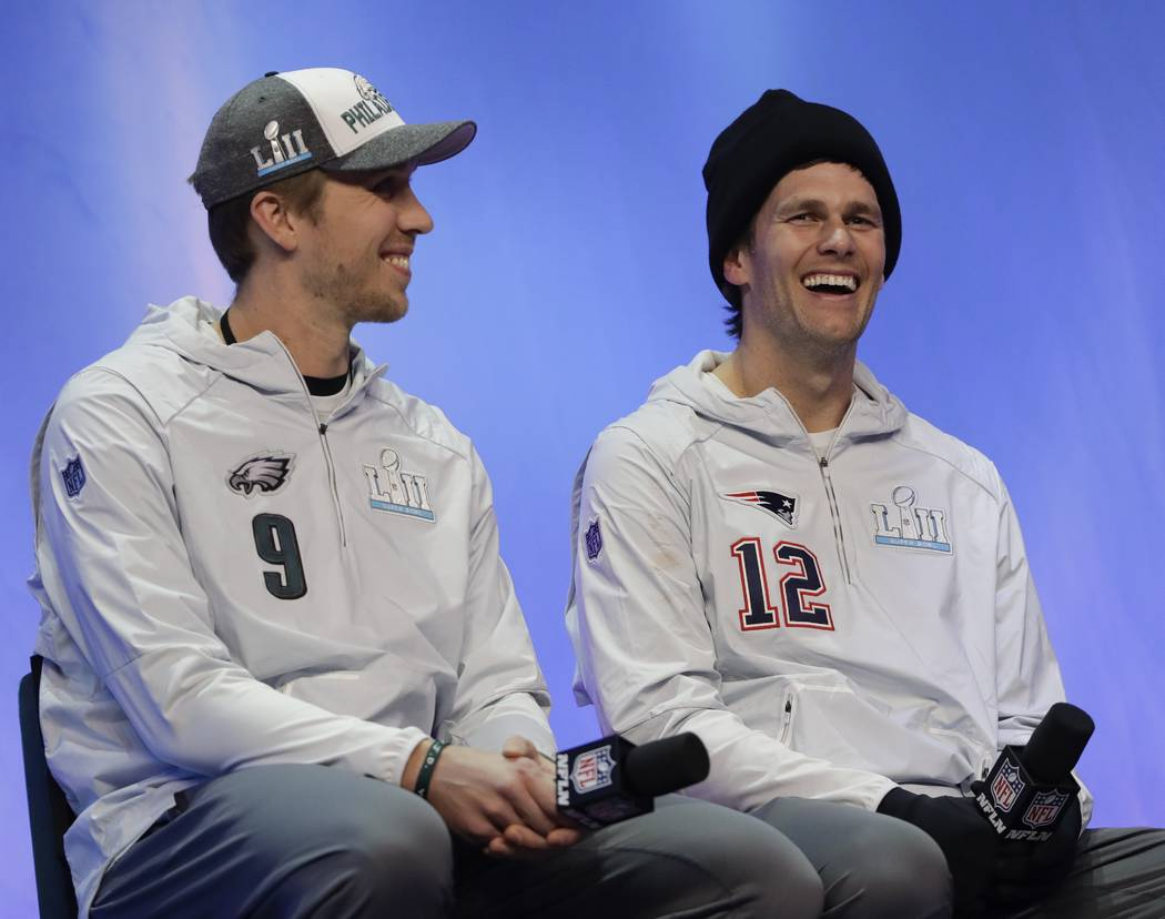 Philadelphia Eagles' Nick Foles and New England Patriots' Tom Brady answer questions during NFL football Super Bowl 52 Opening Night Monday, Jan. 29, 2018, at the Xcel Center in St. Paul, Minn. (A ...