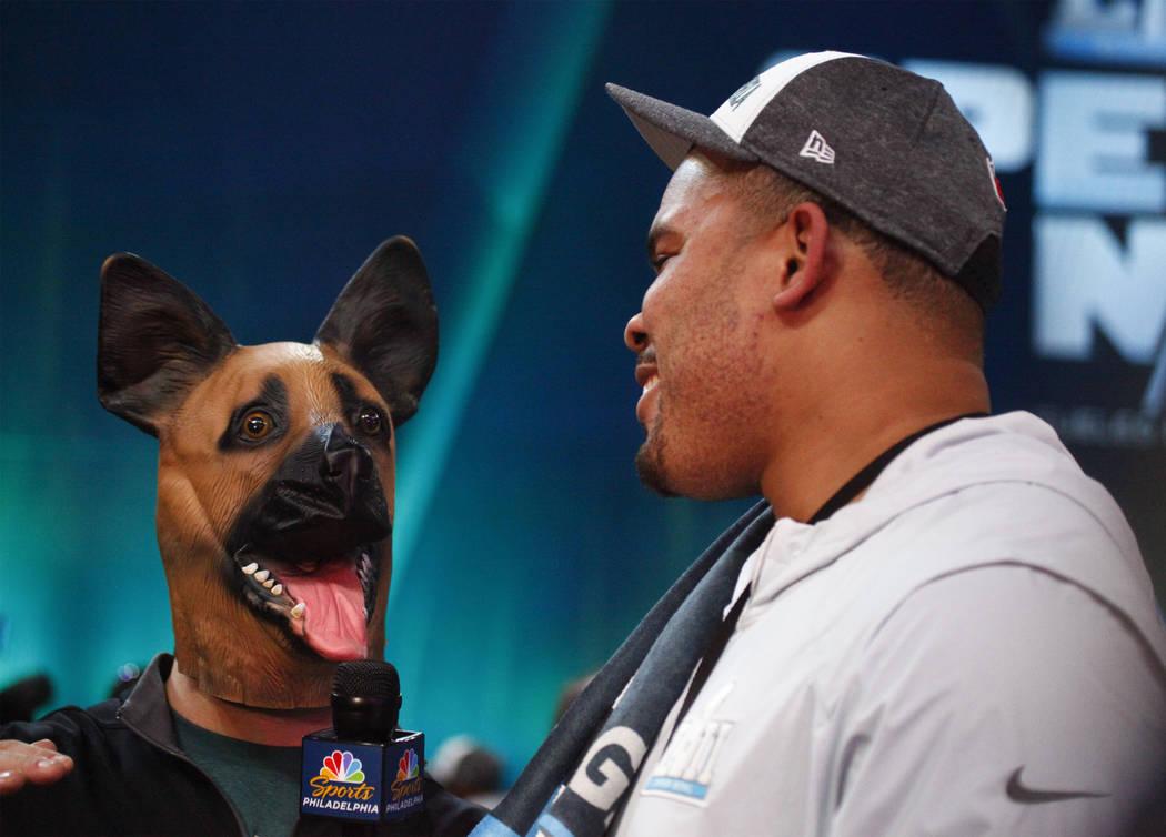 Marc Farzetta wears a dog mask as he interviews Philadelphia Eagles' Brandon Brooks during Super Bowl 52 Opening Night at the Xcel Energy Center in St. Paul, Minn., Monday, Jan. 29, 2018. Heidi Fa ...