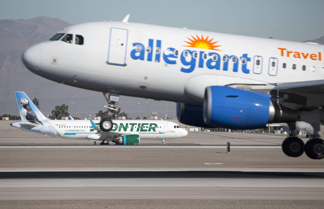 An Allegiant Air flight descends onto the runway as a Frontier Airlines aircraft taxis the tarmac at McCarran International Airport in Las Vegas on Monday, Jan. 22, 2018. (Richard Brian/Las Vegas  ...