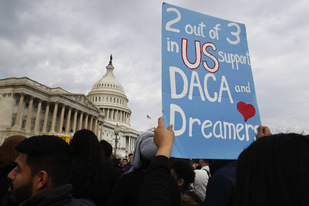 A woman holds up a sign outside the Capitol in support of the Deferred Action for Childhood Arrivals (DACA) program Tuesday, Dec. 5, 2017, on Capitol Hill in Washington. (AP Photo/Jacquelyn Martin)