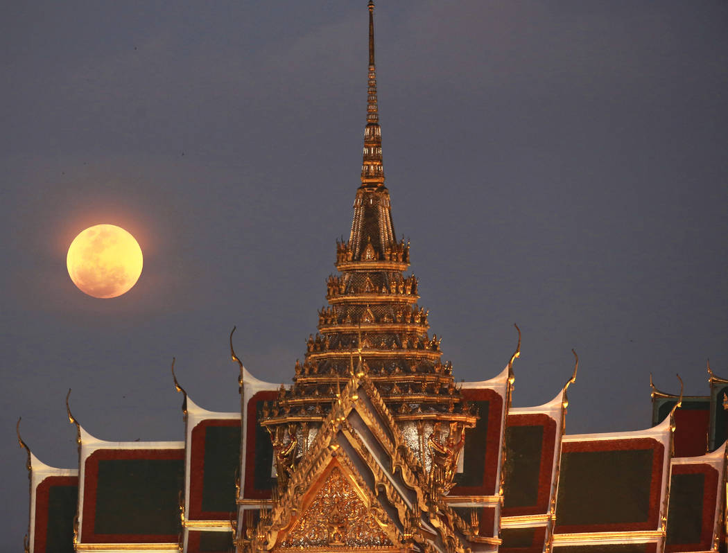 A full moon rises beside the Grand Palace in Bangkok, Thailand , Wednesday, Jan. 31, 2018. The moon is putting on a rare cosmic show. It's the first time in 35 years a blue moon has synced up with ...