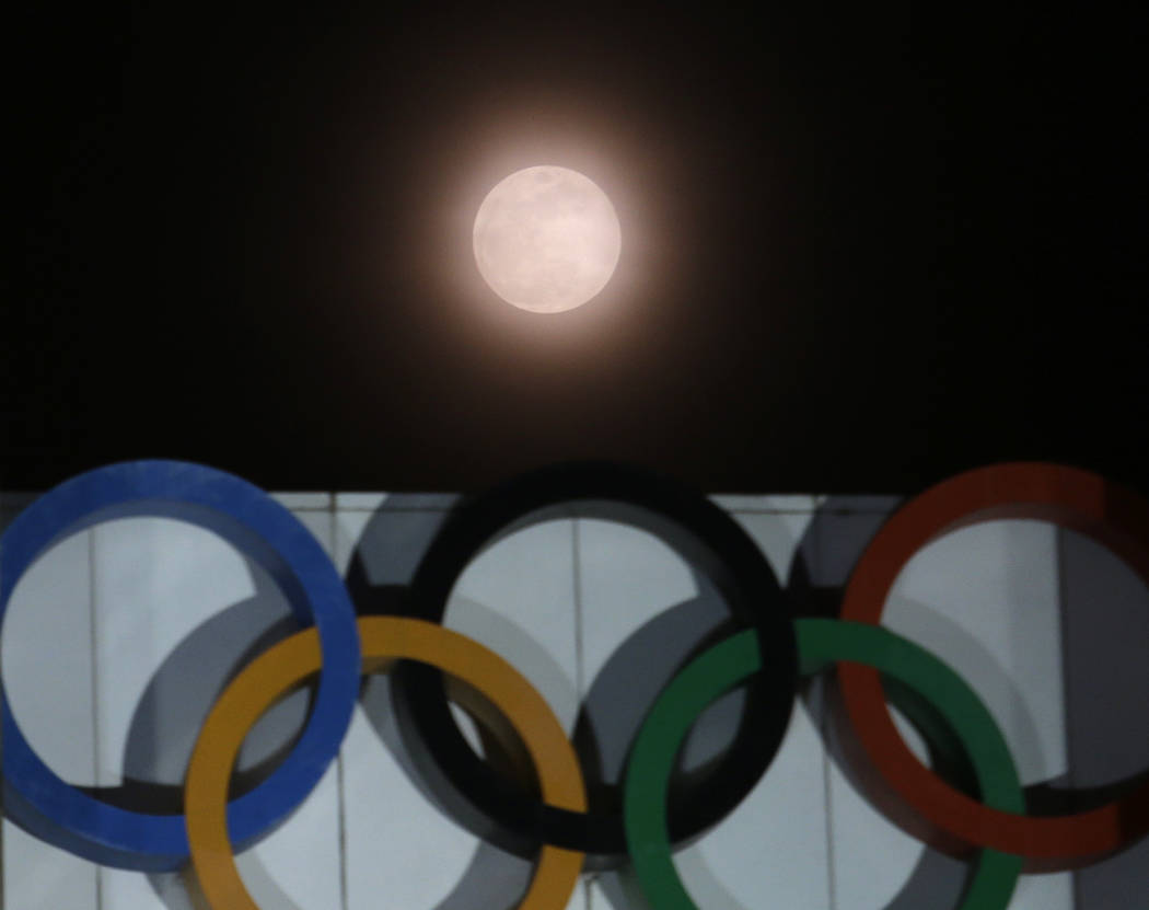 The full moon is seen over the Olympic rings on display at the Peace Gate at the Olympic Park in Seoul, South Korea, Wednesday, Jan. 31, 2018. The moon is putting on a rare cosmic show. It's the f ...